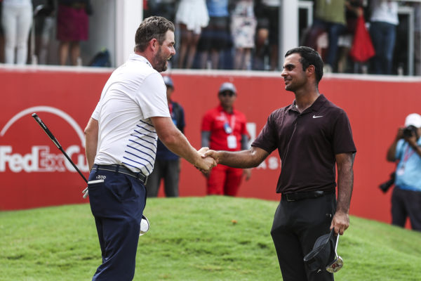Marc Leishman (L) of Australia and Shubhankar Sharma of India shake hands after completing the final round of the CIMB Classic at TPC Kuala Lumpur on October 14, 2018 in Kuala Lumpur, Malaysia.